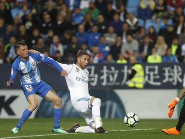 Pemain Real Madrid, Sergio Ramos (tengah) berusaha menghalau bola dari kejaran pemain Malaga, Maxime Lestienne (kiri) pada lanjutan La Liga Santander di Rosaleda stadium, Malaga, (15/4/2018). Madrid menang 2-1. (AP/Miguel Morenatti)