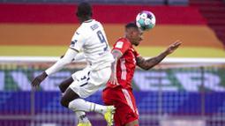 Bek Bayern Munchen, Jerome Boateng, duel udara dengan pemain Hoffenheim, Ihlas Bebou, pada laga Bundesliga di Stadion Allianz Arena, Sabtu (30/1/2021). Bayern Munchen menang dengan skor 4-1. (Sven Hoppe/dpa via AP)
