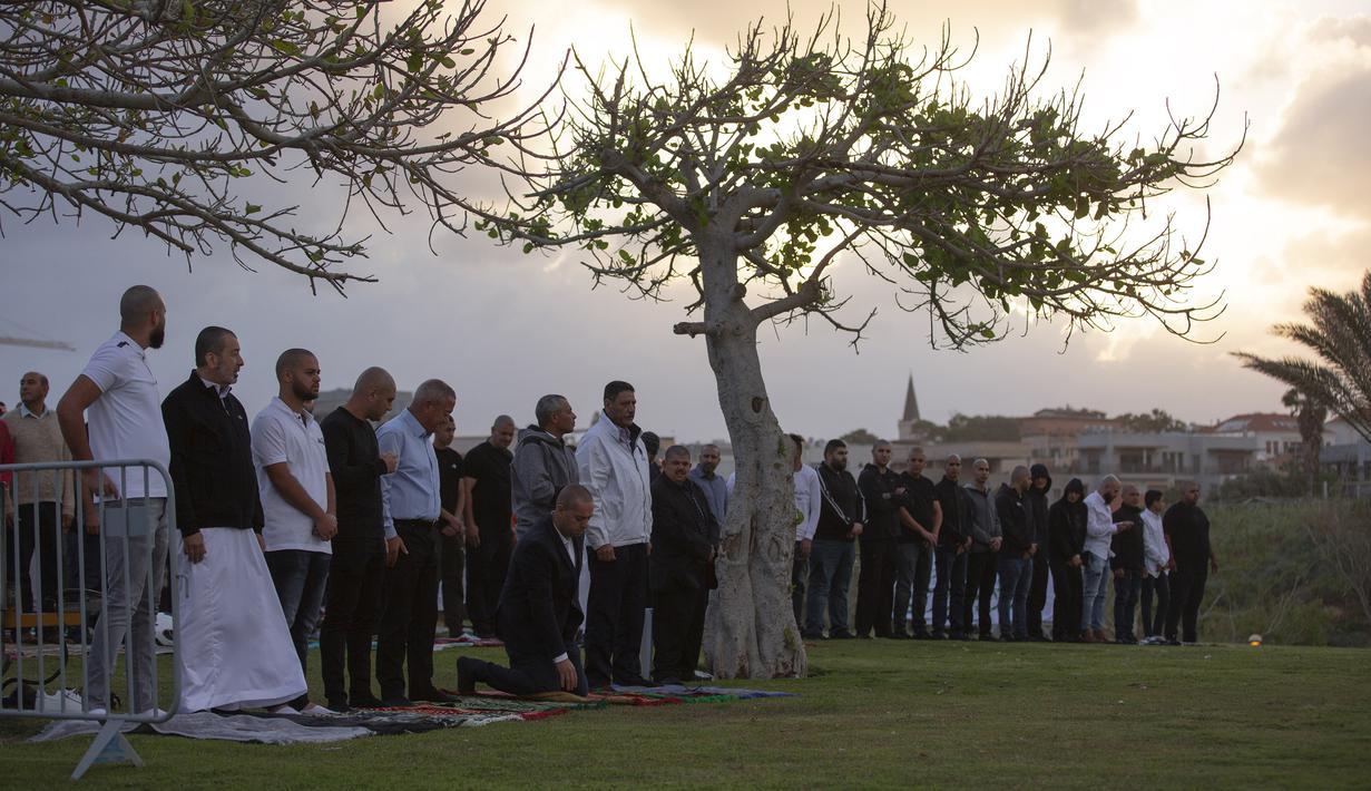 Umat muslim berkumpul untuk melaksanakan salat Idul Fitri yang menandai berakahirnya bulan suci Ramadan di sebuah taman di Jaffa, Israel, Minggu (24/5/2020). Jaffa merupakan kota campuran Yahudi-Arab. (AP Photo/Oded Balilty)