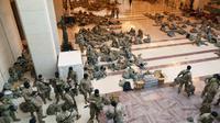 Garda Nasional AS yang sudah memadati bagian dalam gedung untuk berjaga-jaga. Sembari menunggu momen pelatikan Joe Biden, sesekali mereka bergantian beristirahat (AP)