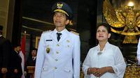 Jokowi dan Iriana kompak mengenakan kemeja baju kemeja putih dengan celana jeans berwarna biru.