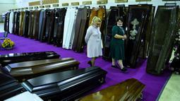 Peserta berjalan di antara peti mati selama pameran pemakaman di Moskow, Rusia pada Rabu (21/10/2020). (Photo by Kirill KUDRYAVTSEV / AFP)