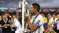 Bek Real Madrid, Raphael Varane, mencium piala merayakan gelar juara Liga Champions di Stadion Millenium, Cardiff, Sabtu (3/6/2017). Madrid menang 4-1 atas Juventus. (AFP/Glyn Kirk)