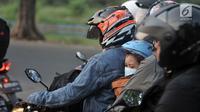 Seorang bocah membonceng sepeda motor diapit ayah dan ibunya di Jalur Kalimalang, Bekasi, Jawa Barat, Rabu (13/6). Kendaraan pemudik yang didominasi roda dua saling berhimpitan di tengah barang bawaan masing-masing. (Merdeka.com/Iqbal S. Nugroho)