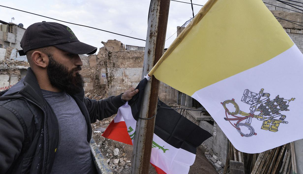 Pekerja mengibarkan bendera Irak dan Takhta Suci Vatikan di tiang-tiang jalan di kota Mosul, Irak, Kamis (4/3/2021). Pemimpin Tertinggi Umat Katolik Paus Fransiskus memulai kunjungan bersejarah ke Irak pada Jumat (5/3), meskipun menghadapi pandemi Covid-19 dan ancaman keamanan. (Zaid AL-OBEIDI/AFP)