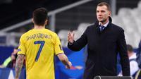 Pelatih Ukraina, Andriy Shevchenko, memberikan selamat kepada anak asuhnya, Mykola Shaparenko, usai melawan Prancis pada laga Kualifikasi Piala Dunia di Stadion Saint Denis, Paris, Kamis (25/3/2021). Kedua tim bermain imbang 1-1. (AFP/Franck Fife)