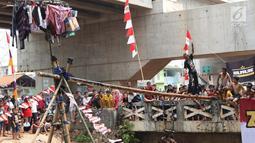 Warga bermain lomba jalan di atas batang pohon pinang di sekitar Kalimalang, Jakarta, Sabtu (17/8/2019). Beragam lomba permainan digelar warga untuk menyemarakkan HUT ke-74 Republik Indonesia. (Liputan6.com/Helmi Fithriansyah)
