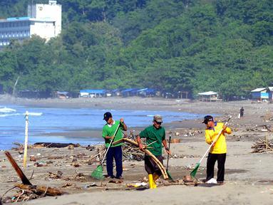 Sukarelawan yang berasal dari warga lokal membersihkan sampah yang berserakan akibat terbawa ombak pasang di kawasan Pantai Citepus, Pelabuhan Ratu, Sukabumi, Jumat (4/1). (Merdeka.com/Arie Basuki)