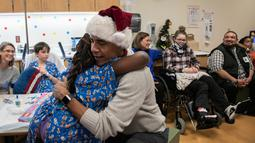 Mantan Presiden AS, Barack Obama memeluk seorang pasien anak di Children's National Medical Center , Washington, Rabu (19/12). Kedatangan Obama yang menyerupai sinterklas itu untuk membagikan hadiah natal kepada anak-anak di sana. (Chuck Kennedy / AFP)