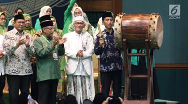Presiden Joko Widodo atau Jokowi memukul bedug saat membuka Harlah ke-93 NU di Jakarta, Kamis (31/1). Jokowi didampingi sejumlah menteri Kabinet Kerja saat menghadiri Harlah ke-93 NU. (Liputan6.com/Angga Yuniar)