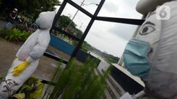 Patung bermasker terlihat di pinggiran Kali Kanal Barat, Cakung, Jakarta, Kamis (25/2/2021). Infeksi virus corona COVID-19 di Indonesia terus meningkat dengan angka terkonfirmasi hingga saat ini sebanyak 1.306.141 pasien. (merdeka.com/Imam Buhori)