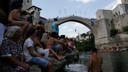 Penonton menyaksikan seorang peserta melompat dari Jembatan Old Mostar pada kompetisi menyelam tradisional ke-452 di Mostar, Bosnia, 29 Juli 2018. Ini merupakan kompetisi selam tahunan yang menjadi salah satu daya tarik Bosnia. (AP/Amel Emric)