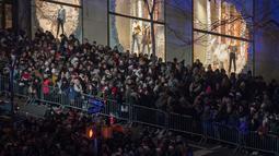 Warga berkumpul untuk menyaksikan upacara tahunan ke-86 penyalaan pohon Natal Rockefeller Center di 50th Street, New York, AS, Rabu (28/11). Pohon yang dipakai merupakan cemara spruce Norwegia setinggi 22 meter dan berat 12 ton. (AP Photo/Mary Altaffer)