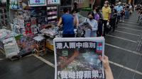 Seorang wanita mencoba mengambil gambar edisi terakhir Apple Daily di depan stan surat kabar di mana orang-orang antre untuk membeli koran di sebuah jalan pusat kota di Hong Kong, Kamis (24/6/2021) Apple Daily mencetak edisi terakhir, Kamis (24/6), setelah 26 tahun beroperasi. (AP Photo/Vincent Yu)