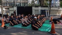 Pasukan Brimob menunaikan ibadah salat Ashar berjamaah disela pengamanan di kawasan Bundaran HI, Jakarta, Rabu (29/5/2019). Di tengah tugas mengamankan situasi, para anggota Brimob tak lupa untuk tetap menjalankan kewajibannya sebagai umat beragama. (Liputan6.com/Faizal Fanani)