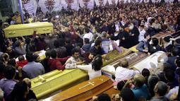 Umat Kristen Mesir menghadiri prosesi pemakaman korban serangan bom di Gereja Koptik St. George, Kota Tanta, utara Kairo, Minggu (9/4). Status keadaan darurat dikeluarkan Mesir selama tiga bulan menyusul dua serangan bom di gereja Koptik. (STRINGER/AFP)