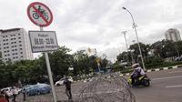 Plang pemberitahuan larangan sepeda motor melintas yang terpampang di jalan Medan Merdeka Barat, Jakarta, Selasa (7/11). Anies meminta ada perubahan agar motor bisa difasilitasi di Jalan MH Thamrin. (Liputan6.com/Faizal Fanani)