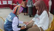 Petugas Kelompok Penyelenggara Pemungutan Suara (KPPS) menjalani pemeriksaan kesehatan oleh petugas medis Puskesmas saat pemungutan suara ulang di TPS 49 Rengas, Ciputat Timur, Tangsel, Rabu (24/4). Pemeriksaan untuk antisipasi menurunnya kesehatan fisik akibat kelelahan. (merdeka.com/Arie Basuki)