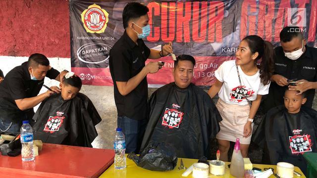 """Warga saat mengikuti cukur gratis yang diselenggarakan oleh Relawan Jokowimotion di Cakung, Jakarta Timur, Sabtu (13/10). Kegiatan ini bertema """"Karena Rapi Itu yang Pertama"""". (Liputan6.com/Andy)"""