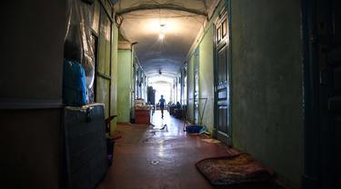 Seorang wanita melewati koridor komunal asrama untuk para pekerja pabrik tekstil Proletarka di Kota Tver, Rusia, 8 Agustus 2020. Zaman keemasan Proletarka diakhiri dengan pecahnya Uni Soviet dan datangnya ekonomi pasar yang membuka perbatasan bagi tekstil murah dari China. (Alexander NEMENOV/AFP)