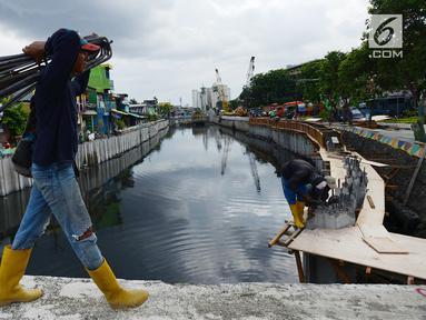 Pekerja membawa besi saat memasang turap atau sheetpile Kali Item, Jakarta, Rabu (2/1). Turap sepanjang 1.900 meter pada sisi kanan dan kiri kali untuk mengantisipasi genangan dan banjir di kawasan tersebut pada musim hujan. (Merdeka.com/Imam Buhori)