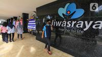 Sejumlah orang berjalan dekat karangan bunga di halaman Kantor PT Asuransi Jiwasraya (Persero), Jakarta, Selasa (15/12/2020). Karangan bunga tersebut berisi ucapan dukungan kepada manajemen baru Jiwasraya dalam penyelamatan polis melalui program restrukturisasi. (Liputan6.com/Faizal Fanani)
