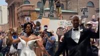 Pasangan pengantin berpose di tengah masa demonstran George Floyd. (dok. Instagram @luxorweddingfilms/ https://www.instagram.com/p/CBGs4OdnF1-/Dinny Mutiah)