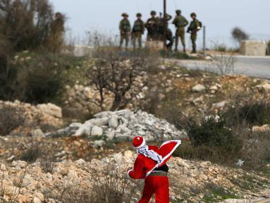 Seorang demonstran Palestina mengenakan kostum Santa Claus melempar batu ke arah pasukan keamanan Israel saat terjadi bentrokan di pos pemeriksaan Atarot di pinggiran utara Yerusalem (19/12). (AFP Photo/Abbas Momani)