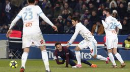 Pemain PSG, Neymar (tengah) jatuh saat berebut bola dengan pemain Marseille pada lanjutan Ligue 1 Prancis di Parc des Princes Stadium, Paris, (25/2/2018). PSG menang 3-0. (AP/Thibault Camus)