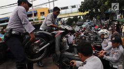 Petugas Dishub DKI mengangkut sepeda motor saat operasi penertiban di Pasar Tanah Abang, Jakarta, Senin (21/5). Banyak preman yang memanfaatkan momen meningkatnya pengunjung pasar Tanah Abang dengan membuka area parkir liar. (Liputan6.com/Arya Manggala)