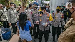 Kapolda Metro Jaya Irjen Pol Fadil Imran membagikan masker kepada anak-anak di Sunter Muara, Tanjung Priok, Jakarta, Selasa (9/2/2021). Kegiatan ini untuk menyadarkan masyarakat akan pentingnya penggunaan masker dalam memutus mata rantai penyebaran COVID-19. (Liputan6.com/Faizal Fanani)