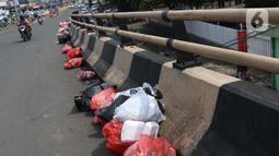 Kantong plastik berisi sampah tergeletak di jalan layang Jalan Raya Bogor, Kabupaten Bogor, Senin (1/6/2020). Minimnya lokasi penampungan sampah semenatara dan kesadaran warga untuk membuang sampah pada tempatnya menjadikan area ini kerap dipenuhi timbunan sampah. (Liputan6.com/Helmi Fihtriansyah)