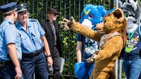 Peserta mengenakan kostum binatang mengajak polisi untuk berpelukan saat parade konvensi Eurofurence di Berlin, Jerman (17/8). Dalam acara peserta mengenakan kostum hewan berbulu. (AFP Photo/Ganjil Andersen)