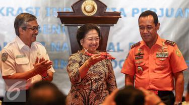 Kepala Basarnas Marsekal Madya FHB Soelistyo (kanan) memberikan cinderamata kepada Ketua Umum DPP PDIP Megawati Soekarnoputri (tengah),  usai  MoU di Kantor Basarnas Jakarta, Rabu (24/8). (Liputan6.com/Faisal Fanani)