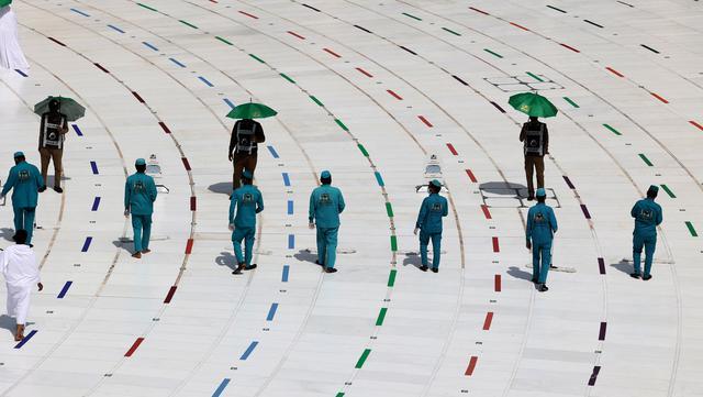 Pekerja membersihkan sekitar Kabah pada awal musim haji di Masjidil Haram, Mekkah, Arab Saudi, Sabtu (17/7/2021). Pemerintah Arab Saudi mengklaim ibadah haji tahun lalu hanya diikuti 1.000 orang, sementara media lokal menyebut ada 10 ribu orang. (FAYEZ NURELDINE/AFP)