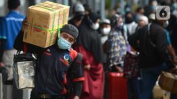 Seorang pria membawa barang bawaan di Stasiun Senen, Jakarta, Selasa (18/5/2021). Berakhirnya larangan mudik pada 17 Mei 2021, Stasiun Senen ramai oleh pemudik susulan yang hendak berangkat ke kampung halaman di Jawa Tengah dan Jawa Timur. (merdeka.com/Imam Buhori)