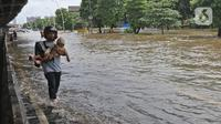 Warga melintasi banjir di Jalan Ahmad Yani, Cempaka Putih, Jakarta, Minggu (23/2/2020). Banjir yang terjadi dari dini hari tadi melumpuhkan akses jalan tersebut. (Liputan6.com/Herman Zakharia)