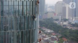 Pekerja membersihkan kaca gedung bertingkat di Jakarta, Jumat (26/02/2021). BP Jamsostek menekankan dua aspek penting terkait pandemi Covid-19, yakni isu kesehatan dan perekonomian dengan jaminan sosial bagi para pekerja dan penerapan K3. (Liputan6.com/Fery Pradolo)