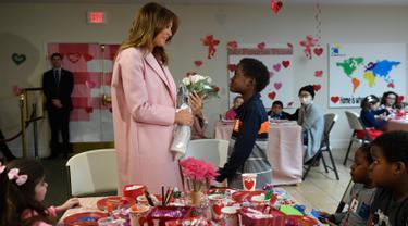 Melania Trump menerima buket bunga dari Amani (13) asal Kenya dalam kunjungannya di rumah sakit National Institutes of Health, Maryland, Kamis (14/2). Melania Trump menghabiskan momen Hari Valentine bersama anak-anak di rumah sakit.  (AP/Susan Walsh)