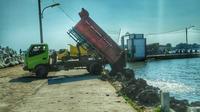 Truk-truk ini membuang lumpur hasil normalisasi Banjir Kanal Timur Semarang di tambak bandeng produktif milik warga tanpa dialog. (foto : Liputan6.com / Edhie Prayitno Ige)
