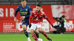 Gelandang Brest, Haris Belkebla (kanan) menguasai bola dibayangi gelandang Lyon, Bruno Guimaraes dalam laga lanjutan Liga Prancis 2020/21 pekan ke-26 di The Francis Le Ble Stadium, Brest, Jumat (19/2/2021). Brest kalah 2-3 dari Lyon. (AFP/Fred Tanneau)