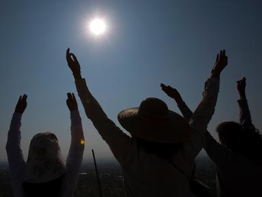 Sejumlah warga mengangkat tangan selama upacara menyambut fenomena equinox di depan Piramida Matahari, Teotihuacan, Meksiko, Senin (20/3). Fenomena equinox merupakan peristiwa ketika matahari tepat berada di atas khatulistiwa. (AP/Rebecca Blackwell)