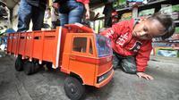 Seorang anak melihat mainan kayu di kawasan Kalibata, Jakarta, Rabu (17/10). Sukma merupakan satu dari segelintir pedagang mainan lokal di Ibu Kota yang masih bertahan dari ekspansi pasar impor. (Merdeka.com/Iqbal S. Nugroho)