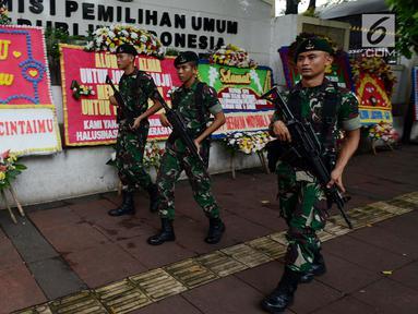 Sejumlah tentara bersenjata berjalan melintasi karangan bunga yang ada di Gedung Komisi Pemilihan Umum (KPU), Jakarta, Sabtu (20/4). Karangan bunga terus berdatangan ke Gedung KPU. (merdeka.com/Imam Buhori)