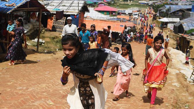 Bocah-bocah Rohingya mengenakan pakaian baru selama perayaan Idul Adha di kamp pengungsi Thangkhali, Bangladesh, Rabu (22/8). Wajah riangnya senapas dengan baju baru yang dikenakan di hari bahagia ini. (Dibyangshu SARKAR / AFP)