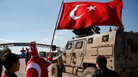 Isikli Tosun Baba (60) melambaikan bendera saat pasukan Turki bergerak melewatinya di Oncupinar, Kilis, Turki, Minggu (28/1). Aksi itu dilakukan untuk mendukung serangan pasukan Turki ke kantung Kurdi di Afrin, Suriah. (AP Photo/Lefteris Pitarakis)