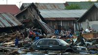 Warga mencari barang-barang yang tertimbun puing rumah mereka yang roboh akibat gempa dan tsunami di Palu, Sulawesi Tengah, Sabtu (29/9). Dampak dari bencana itu menyebabkan sejumlah bangunan hancur dan ratusan jiwa meninggal dunia. (AFP/MUHAMMAD RIFKI)