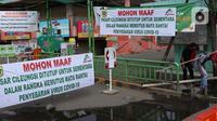 Warga melintasi palang bambu penutup pintu masuk kawasan Pasar Cileungsi, Kabupaten Bogor, Selasa (2/6/2020). Penutupan sementara kegiatan jual beli di Pasar Cileungsi terkait adanya tujuh pedagang yang positif terinfeksi virus COVID-19. (Liputan6.com/Helmi Fithriansyah)