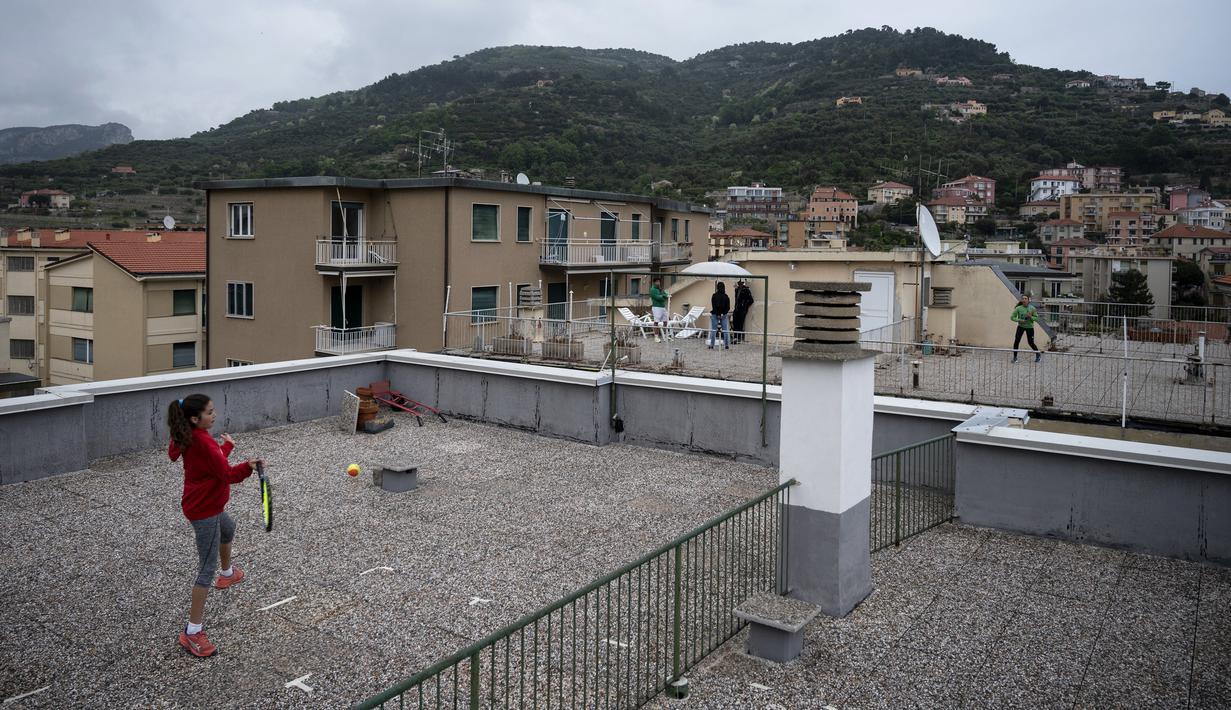 Carola Pessina bermain tenis dengan Vittoria Oliveri di atas atap rumah mereka selama lockdown COVID-19 di Finale Ligure, Wilayah Liguria, Italia (19/4/2020). Setiap hari Carola, 11, dan Vittoria, 13, bermain tenis dari satu atap ke atap lain di rumah mereka untuk berlatih. (AFP/Marco Bertorello)