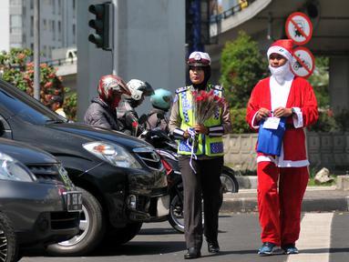 Menyambut Hari Natal 2015, anggota Kepolisian Polres Jakarta Barat kenakan topi Sinterklas dan bagikan bunga serta masker kepada pengguna jalan di kawasan Tomang, Jakarta, Rabu (23/12). (Liputan6.com/Yoppy Renato)